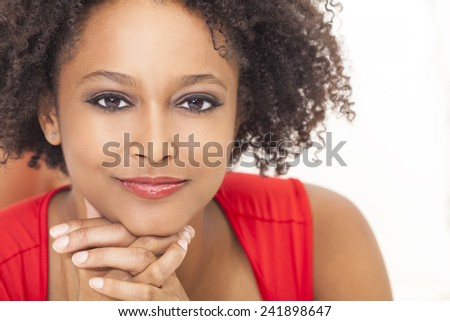 A beautiful mixed race African American girl or young woman wearing a red dress looking happy and smiling - stock photo