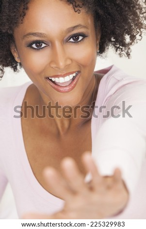 A beautiful mixed race African American girl or young woman with perfect teeth, looking happy and smiling reaching hand out towards camera - stock photo