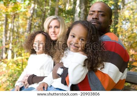 A beautiful mixed race family enjoying the park - stock photo