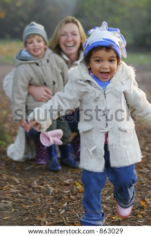 A beautiful mixed race girl runs towards the camera laughing while over her shoulder you see a young mother with her son. - stock photo