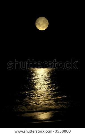 A beautiful moon glowing on the water of the ocean - stock photo