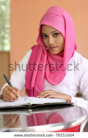 A beautiful muslim girls writing a diary book on the table - stock photo