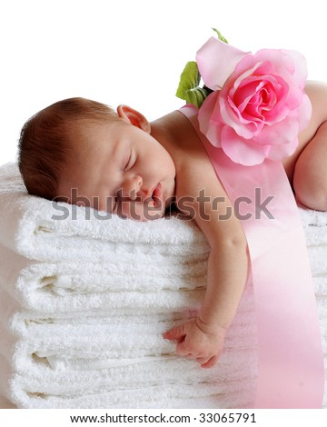A beautiful newborn sleeping soundly on a stack of white towels, a ribbon and pink rose on her back. - stock photo