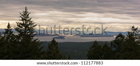 A beautiful panorama of the San Juan Islands, in northwest Washington, on an overcast afternoon.  Canada's Vancouver Island is visible in the distance. - stock photo