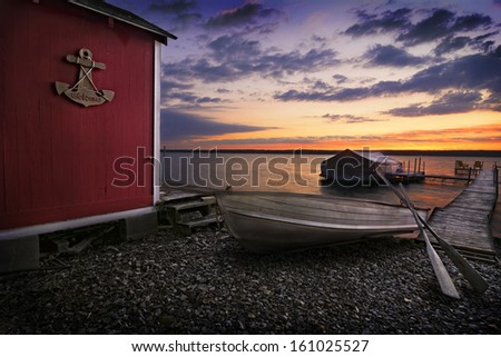 A beautiful place to watch a sunrise on Lake Cayuga in the Finger lakes region of New York state. To the left is a red storage shed with a wood anchor sign that says Welcome on it.  - stock photo