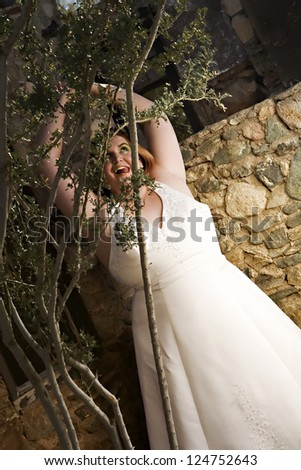 A beautiful plus size bride with green eye make-up posing in her wedding dress - stock photo