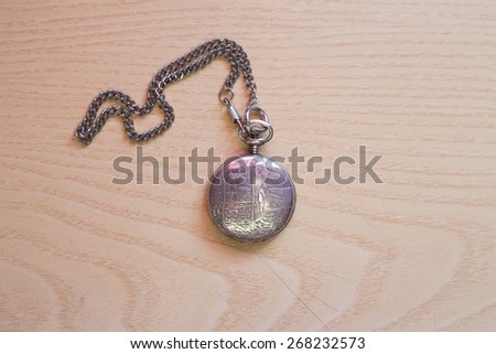 A beautiful pocket old style vintage clock on watch chain. - stock photo