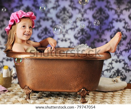 A beautiful preschooler in a bath bonnet and copper tub watching the air-born bubbles around her. - stock photo