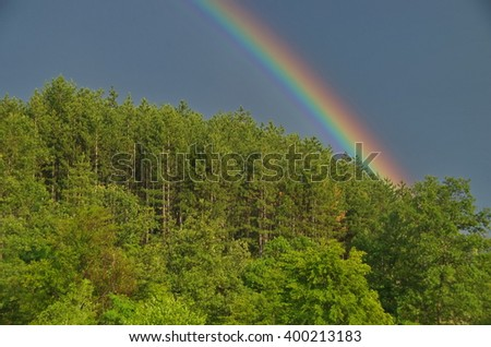 A beautiful rainbow in the cloudy sky, Bulgaria - stock photo