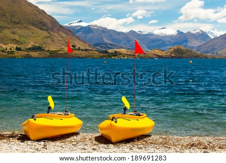 A Beautiful Recreation Area on handicap snowy mountains with a Couple Colorful Kayaks on Lake Wanaka New Zealand, Southern Alps. - stock photo