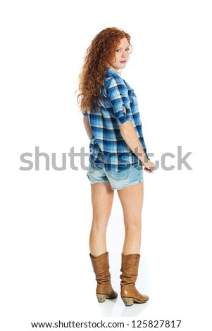 A beautiful redhead looking back over her shoulder. - stock photo