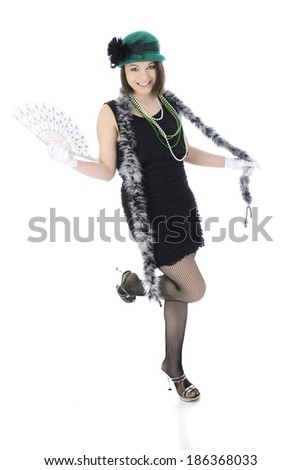 """A beautiful Roaring 20s teen """"flapper""""  happily kicking a leg while fanning herself with another.  On a white background. - stock photo"""