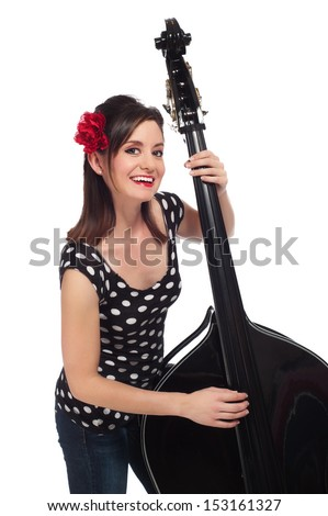 A Beautiful Rockabilly Girl Smiling and Playing a Black Stand-Up Bass. - stock photo