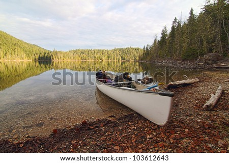 A beautiful, serene view of a calm wilderness lake and a canoe resting on the lakeshore. - stock photo