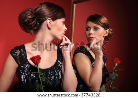A beautiful sexy women wearing an evening dress and holding a red rose looking at her reflection in the miror on red background - stock photo