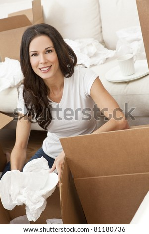 A beautiful single young woman unpacking boxes and moving into a new home. - stock photo