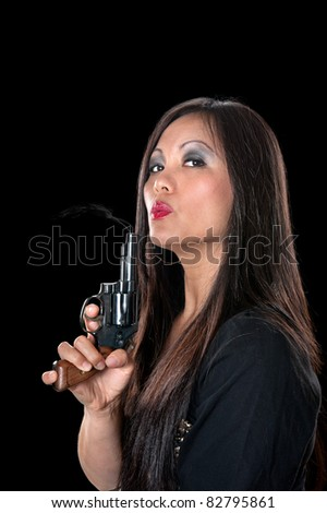 A beautiful, sinister Asian woman holding a pistol and blowing on the smoke coming out of the barrel. - stock photo