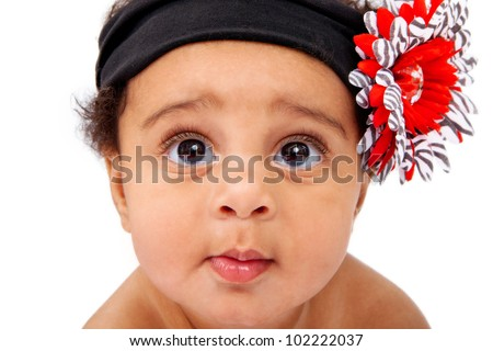 A beautiful six month old baby girl wearing a black headband with a big flower against a white background - stock photo