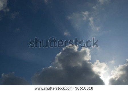 A beautiful sky filled with clouds and a ray of sun - stock photo