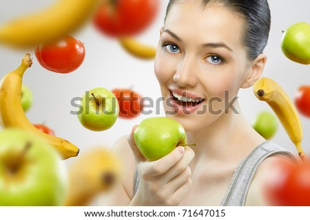 A beautiful slender girl eating healthy fruit - stock photo