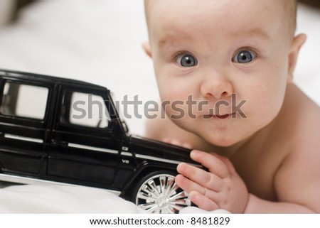 A beautiful smiling baby playing with a toy - stock photo
