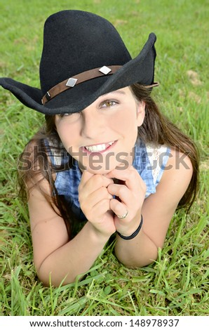 A beautiful smiling girl with western style hat lying in the grass. - stock photo