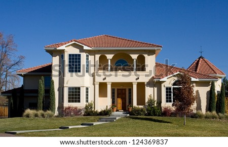 A beautiful Spanish-inspired luxury home, with green lawn and blue sky. - stock photo