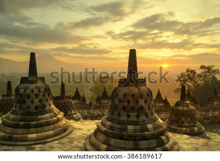 A beautiful sunrise at Borobudur Temple in Indonesia.  The temple is a  Buddhist stupa dating from the 8th century, and it is also a UNESCO World Heritage Site. - stock photo