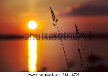 A beautiful sunset by the sea in Finland. Image taken in the summer. Image also has a vintage effect. - stock photo