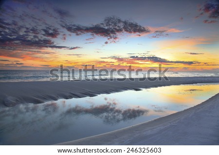 A Beautiful Sunset Reflected in a Tide Pool at the Beach - stock photo