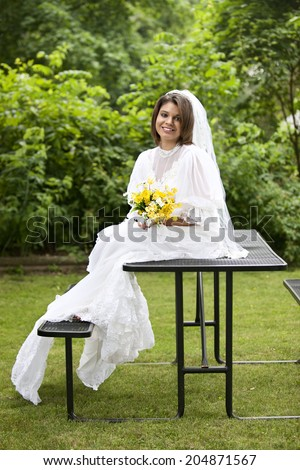 A beautiful teen bride happily sitting on a picnic table. - stock photo