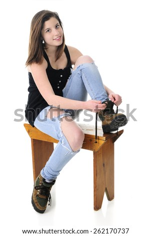 A beautiful teen girl looking at the viewer as she puts on her work boots.  On a white background. - stock photo