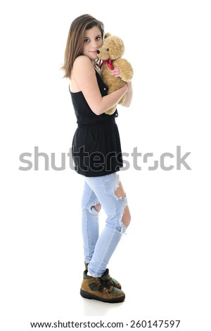 A beautiful teen girl lovingly hugging a generic tan Teddy Bear.  On a white background. - stock photo
