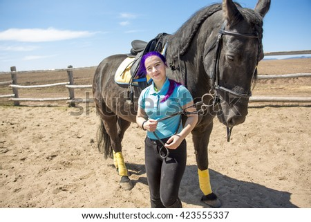 A Beautiful teen girl on the farm with her horse. - stock photo