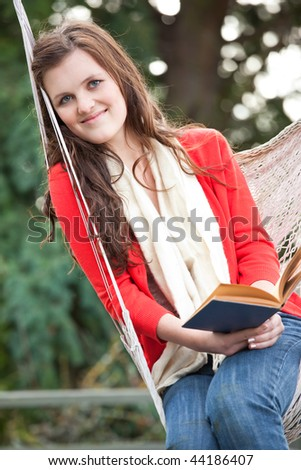 A beautiful teenager sitting on a hammock reading a book - stock photo