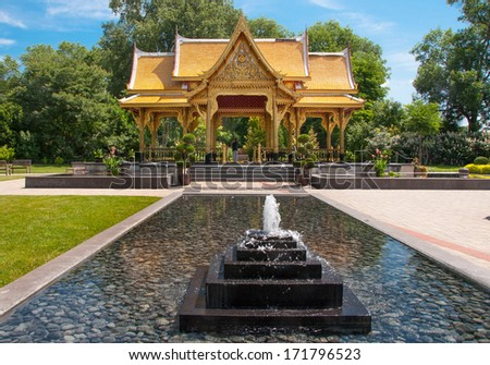 A beautiful Thai Pavilion stands surrounded by bubbling fountains at a Wisconsin public gardens. - stock photo