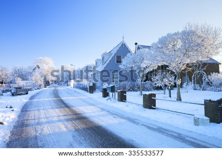 A beautiful tranquil village in winter. Photographed on the morning after of one of the coldest nights recorded in history of The Netherlands at a temperature of -20C. - stock photo