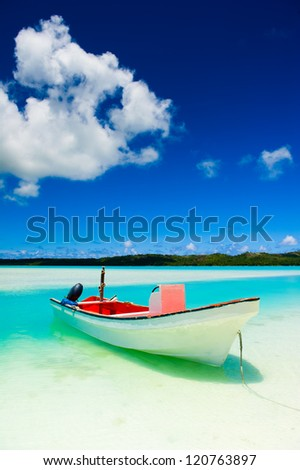 A beautiful tropical island beach with colourful boat in the foreground - stock photo