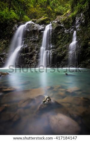 A beautiful tropical waterfall and pool in Hawaii. - stock photo