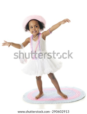 A beautiful two year old African American all gussied up in her petticoat, pearls, hat and purse.  She's barefoot and standing on a rag rug. - stock photo