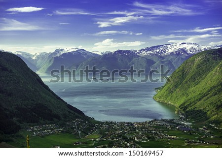 A beautiful valley in the north of Norway, with a ferry that leaves the port. - stock photo