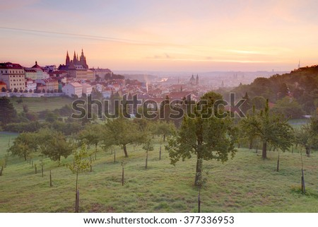 A beautiful view of Prague in morning fog ~ A panorama over Prague Old Town with majestic Prague Castle and St. Vitus Cathedral on the left and sunrise sky with rosy clouds in the background - stock photo