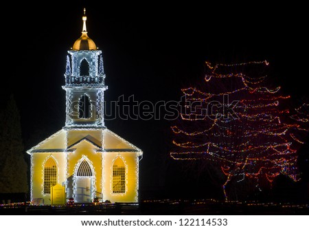 A beautiful village church with bell tower, decorated for Christmas. - stock photo