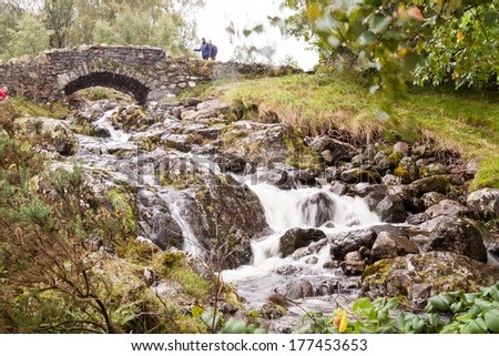 A beautiful waterfall by an old bridge in the Lake District, England. Misty weather. - stock photo
