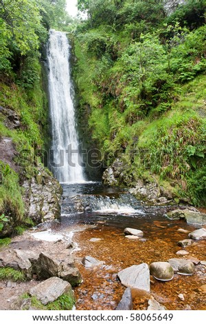 A beautiful waterfall in the  summer time in the forest - stock photo