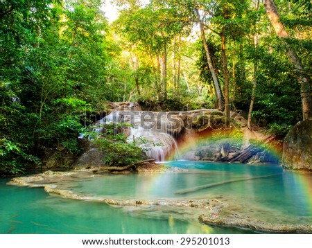 A beautiful waterfall with rainbow in deep forest of Erawan National Park in Kanchanaburi Province , Thailand - stock photo