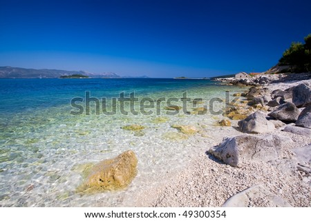 A beautiful white stone beach with clear blue water off the coast of Korcula. - stock photo
