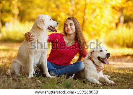 A beautiful woman and her dogs (Labrador retriever) posing in autumn park. Red and orange leaves around. - stock photo