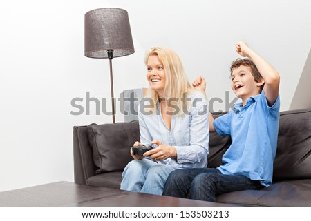 A beautiful woman and her teenage son at home, sitting on a couch playing a video game. - stock photo