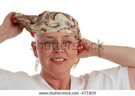 A beautiful woman, bald from chemotherapy,  prepares to remove the scarf covering her head.  Second in a sequence. - stock photo